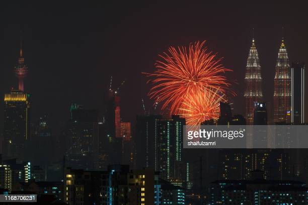 fireworks explode over the petronas twin towers during the midnight display on 45th anniversary of petronas at downtown kuala lumpur. - shaifulzamri stock pictures, royalty-free photos & images