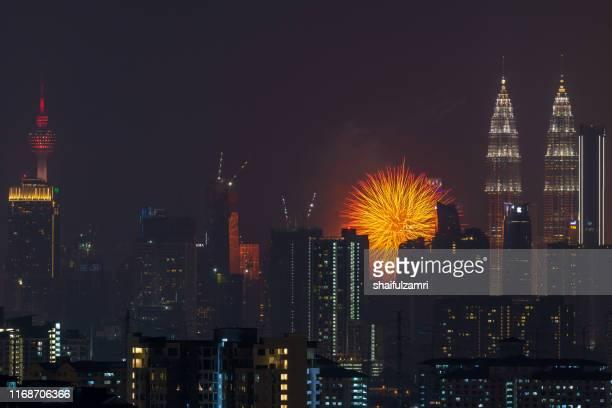 fireworks explode over the petronas twin towers during the midnight display on 45th anniversary of petronas at downtown kuala lumpur. - shaifulzamri stockfoto's en -beelden
