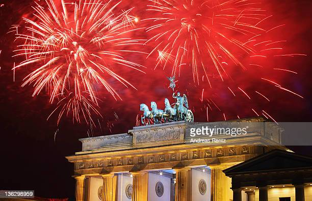 Fireworks explode over the Quadriga statue atop the Brandenburg Gate on New Year's Eve on January 1 2012 in Berlin Germany According to the media up...