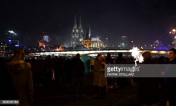 Fireworks explode over the river Rhine in front of the Great Saint Martin Church and the Cologne Cathedral during New Year's celebrations in Cologne...