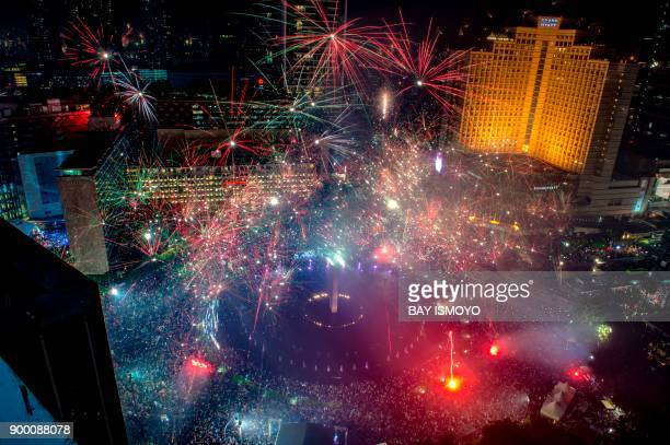 Fireworks explode over the Selamat Datang Monument in downtown Jakarta on January 1 2018 during New Year celebrations / AFP PHOTO / BAY ISMOYO