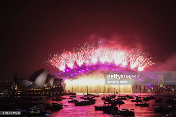 Fireworks explode over the Sydney Harbour Bridge and the Sydney Opera House in the midnight display during New Year's Eve celebrations on January 1...