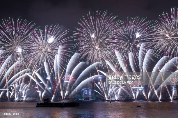 TOPSHOT Fireworks explode over Victoria harbour during New Year celebrations in Hong Kong on January 1 2018 / AFP PHOTO / DALE DE LA REY