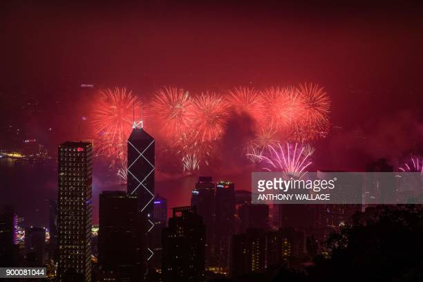 Fireworks explode over Victoria harbour during New Year celebrations in Hong Kong on January 1 2018 / AFP PHOTO / Anthony WALLACE