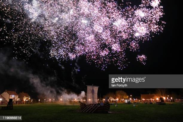 Fireworks explode overhead as a Viking longship is prepared for burning during New Year's Eve celebrations at the Flamborough Fire Festival on...
