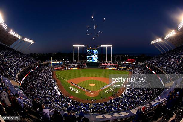 Fireworks explode overhead as the Baltimore Orioles and the Kansas City Royals stand on the baseline during the national anthem prior to Game Three...