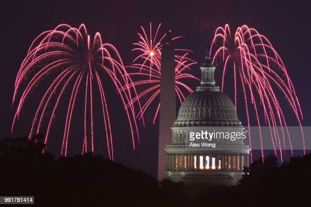 Fireworks explode overhead at the US Capitol and the Washington Monument on Independence Day July 4 2018 in Washington DC Americans celebrated the...