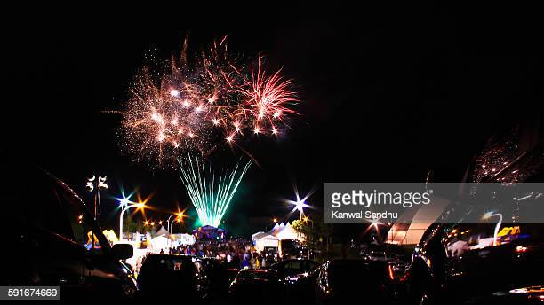 fireworks exploding above crowd of spectators - diwali celebration stock photos and pictures