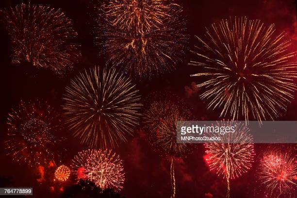 Fireworks exploding in red sky