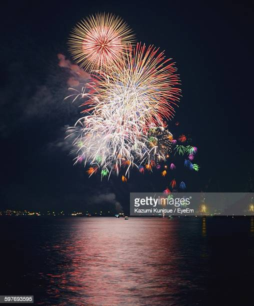 Fireworks Exploding Over City By Sea Against Sky