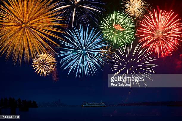 Fireworks exploding over cruise ship in bay, Seattle, Washington, United States