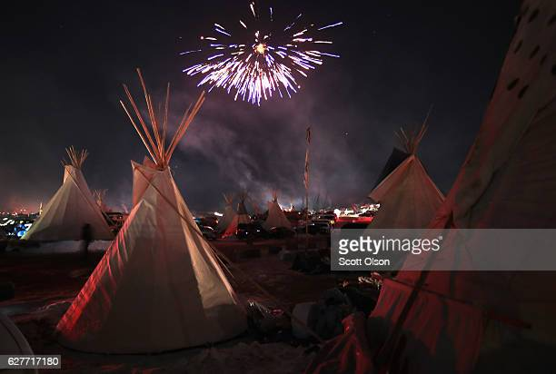 Fireworks fill the night sky above Oceti Sakowin Camp as activists celebrate after learning an easement had been denied for the Dakota Access...