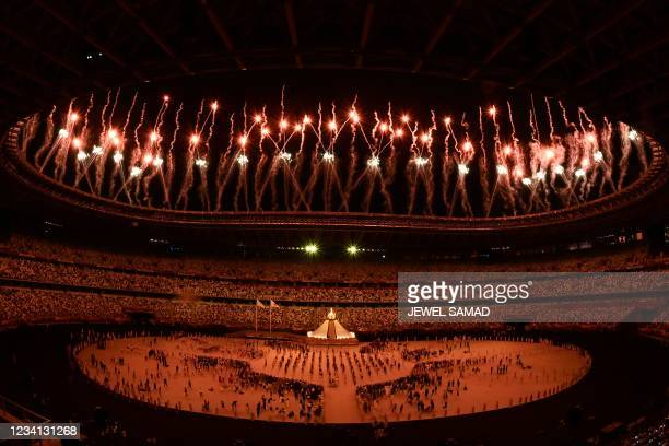 Fireworks go off around the Olympic Stadium after the lighting of the Olympic Flame during the opening ceremony of the Tokyo 2020 Olympic Games, in...