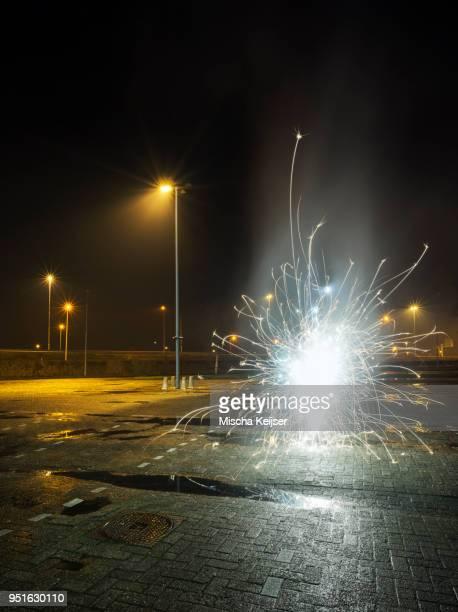 Fireworks going off in a car park, on new years eve, Heerenveen, Friesland, Netherlands