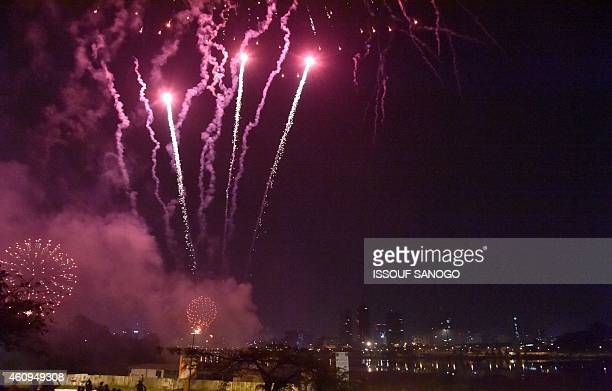 Fireworks illuminate the night sky over the Ebrie Lagoon in Abidjan during New Year celebrations January 1 2015 in Ivory Coast AFP PHOTO / ISSOUF...