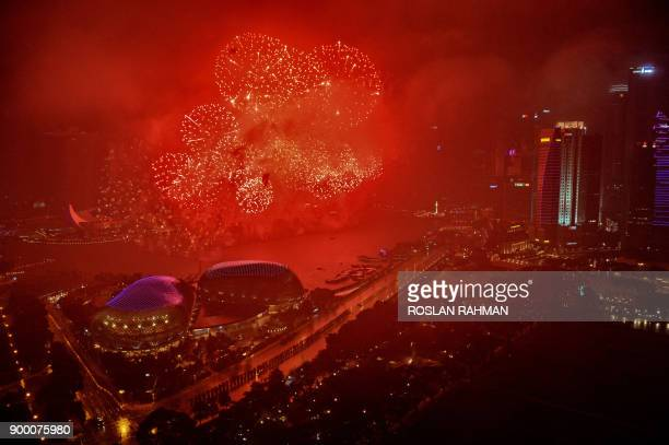 TOPSHOT Fireworks illuminate the skyline as the clock strikes midnight during New Year's Eve celebrations in Singapore early on January 1 2018 / AFP...