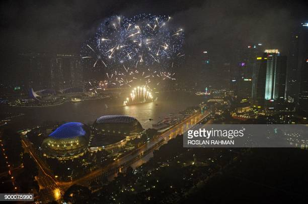 Fireworks illuminate the skyline as the clock strikes midnight during New Year's Eve celebrations in Singapore early on January 1 2018 / AFP PHOTO /...