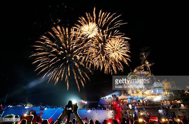Fireworks illuminate the Soviet cruiser Mikhail Kutuzov, which was used as a stage for a patriotic rock concert during a bikers' festival in the...