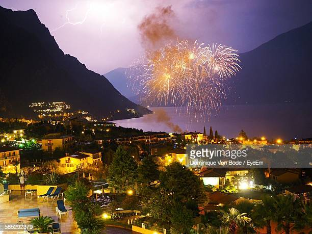 Fireworks In Illuminated Town By Sea Against Sky At Night
