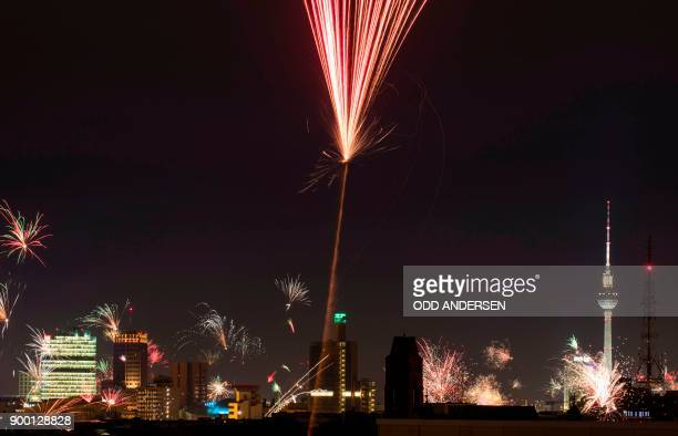 Fireworks is seen over the city skyline with the landmark TV tower as the German capital celebrates the arrival of a new year in Berlin on January 1...