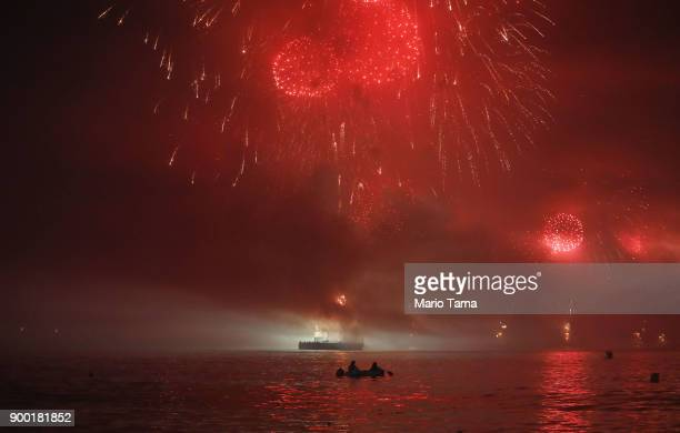 Fireworks launched from barges explode over vessels floating near Copacabana beach on January 1 2018 in Rio de Janeiro Brazil Fireworks were launched...