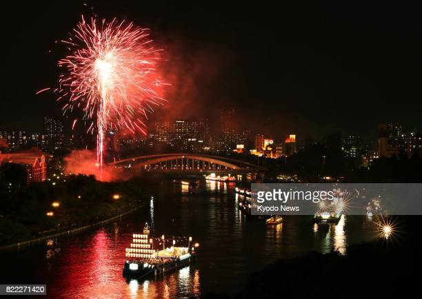 Fireworks light excursion boats on the Okawa River from above in the traditional 'Funatogyo' boat procession in the climax of the Tenjin Matsuri...