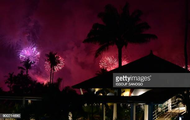 TOPSHOT Fireworks light the night sky over Abidjan during New Year celebrations on January 1 2018 / AFP PHOTO / ISSOUF SANOGO