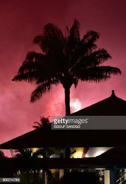 Fireworks light the night sky over Abidjan during New Year celebrations on January 1 2018 / AFP PHOTO / ISSOUF SANOGO