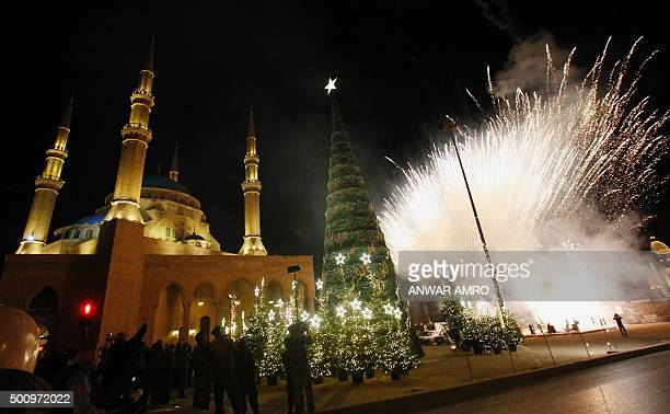 Fireworks light the sky as a Christmas tree designed by Lebanese fashion designer Elie Saab is lit in front of the AlAmin mosque in the capital...