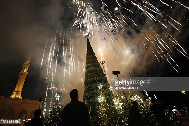 TOPSHOT Fireworks light the sky as a Christmas tree designed by Lebanese fashion designer Elie Saab is lit in front of the AlAmin mosque in the...