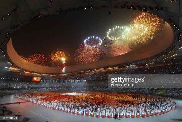 Fireworks light the sky as the Olympic flame burns during the opening ceremony of the 2008 Beijing Olympic Games in Beijing on August 8, 2008. The...