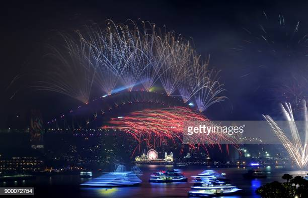 Fireworks light the sky over the Harbour Bridge during New Year's Eve celebrations in Sydney early on January 1 2018 / AFP PHOTO /