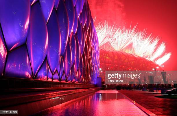 Fireworks light the sky over the National Aquatics Center and the National Stadium during the Opening Ceremony for the 2008 Beijing Summer Olympics...