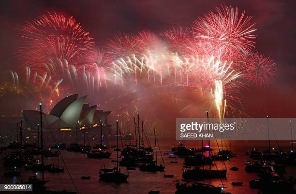 TOPSHOT Fireworks light the sky over the Opera House and Harbour Bridge during New Year's Eve celebrations in Sydney early on January 1 2018 / AFP...