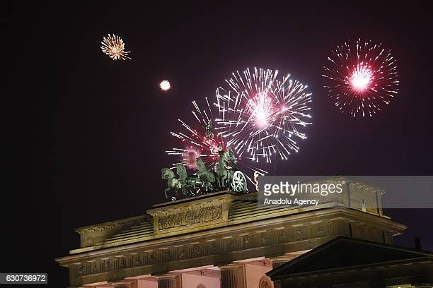 Fireworks light the sky over the Quadriga statue a top the Brandenburg Gate during the New Year's celebrations in Berlin Germany on January 01 2017