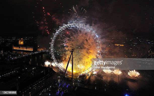 Fireworks light up The London Eye ferris wheel just after midnight on January 1 2012 in London England Thousands of people lined the banks of the...