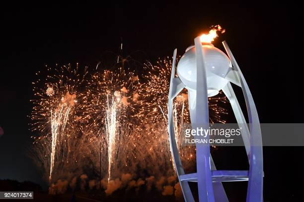 TOPSHOT Fireworks light up the night sky behind the Olympic cauldron during the closing ceremony of the Pyeongchang 2018 Winter Olympic Games at the...