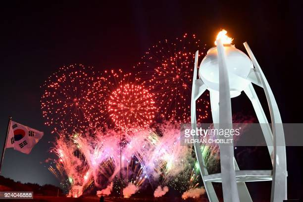 TOPSHOT Fireworks light up the night sky outside the closing ceremony as the Olympic cauldron is seen at the Pyeongchang 2018 Winter Olympic Games at...