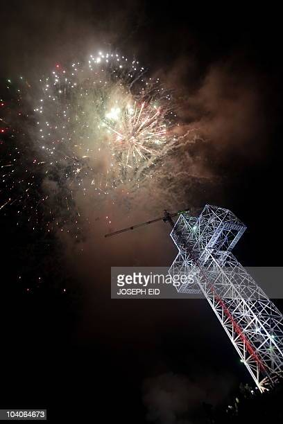 Fireworks light up the skies above a towering cross on the eve of the Elevation of the Holy Cross in the village of Qanat Bekish in the Lebanese...