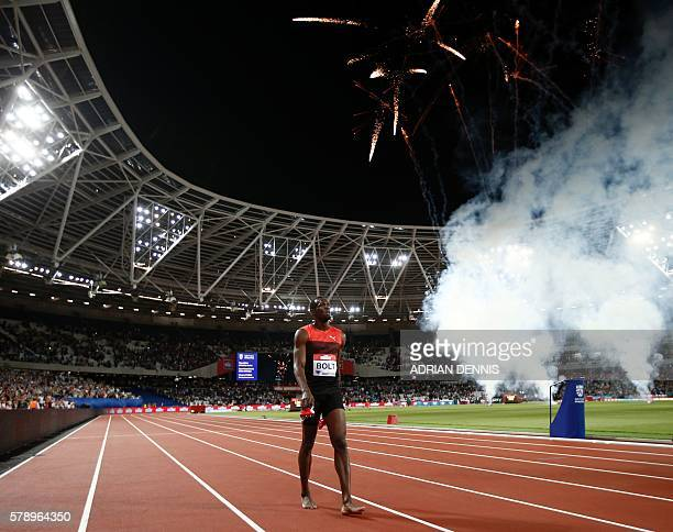 Fireworks light up the sky as Jamaica's Usain Bolt interacts with spectators after winning the men's 200m at the IAAF Diamond League Anniversary...