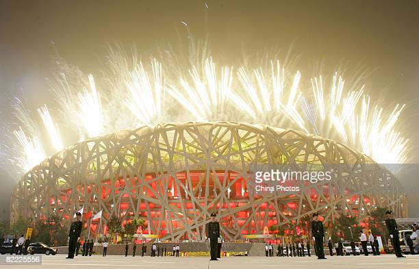 Fireworks light up the sky as paramilitary policemen stand guard outside the National Stadium during the Opening Ceremony for the Beijing 2008...