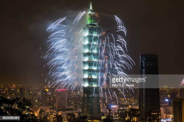 Fireworks light up the Taiwan skyline and Taipei 101 during New Years Eve celebrations just after midnight on January 1 2018 in Taipei Taiwan