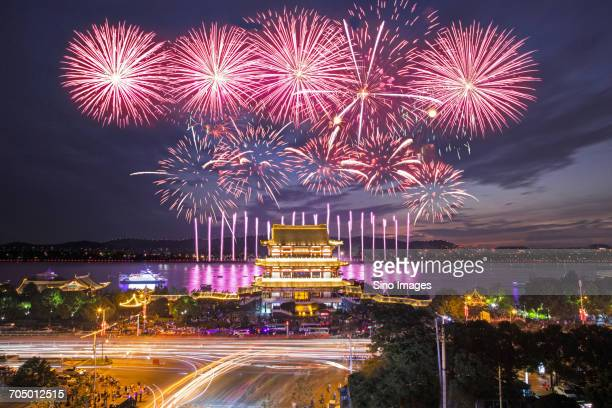 fireworks over illuminated city - hunan province stock pictures, royalty-free photos & images