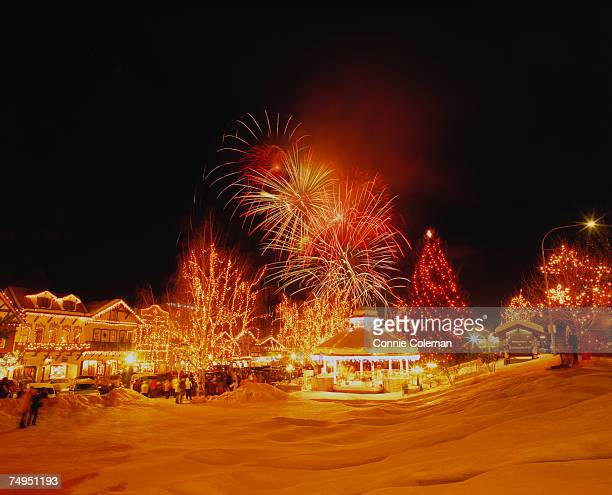 fireworks over illuminated, snow covered park - leavenworth washington stock photos and pictures