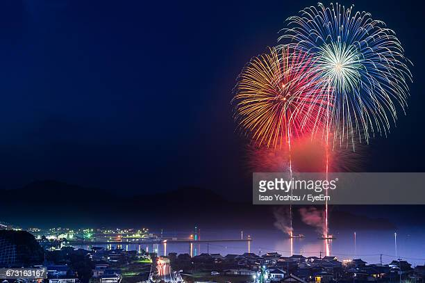 Fireworks Over Lake By Illuminated City At Night