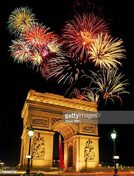 fireworks over the arc de triomphe - arc de triomphe photos et images de collection
