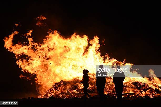 Fireworks technicians stand in front of a large bonfire after a public fireworks display in Driffield Northern England on November 1 held prior to...