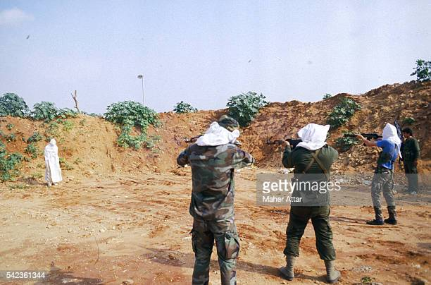 A firing line of four Amal militia take aim at a Lebanese murderer wrapped from head to foot in a white sheet