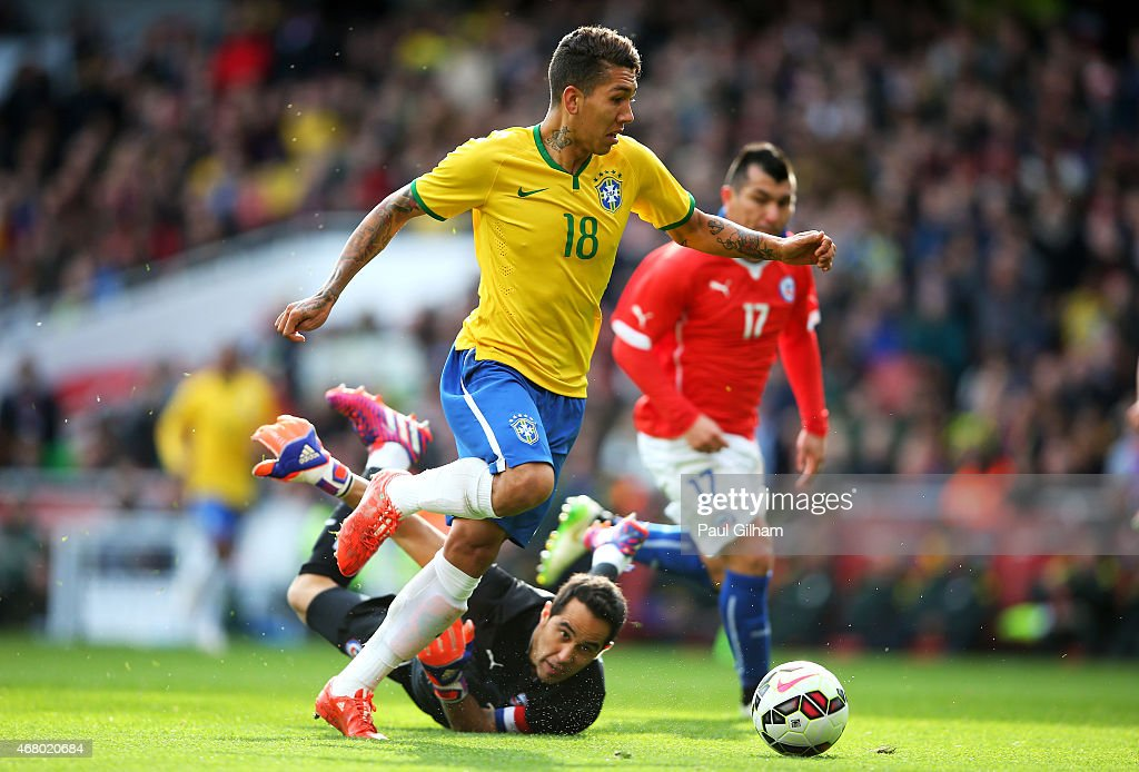 Firmino of Brazil rounds goalkeeper Claudio Bravo of Chile to score the opening goal during the international friendly match between Brazil and Chile at the Emirates Stadium on March 29, 2015 in London, England.