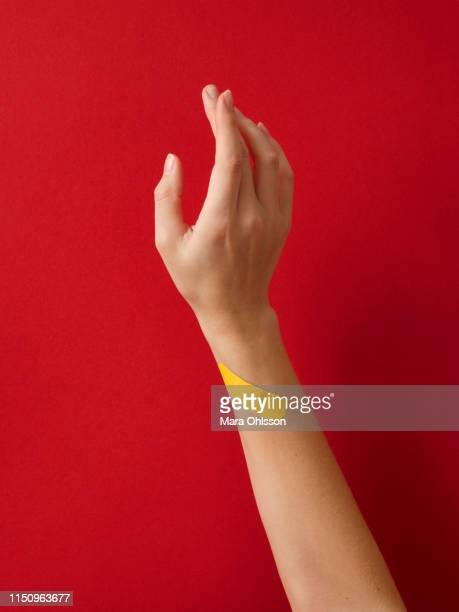 first aid adhesive plaster on woman's wrist against red background - wrist stock pictures, royalty-free photos & images